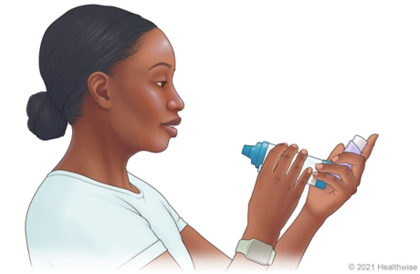 Person holding inhaler and spacer so that inhaler mouthpiece is at bottom.