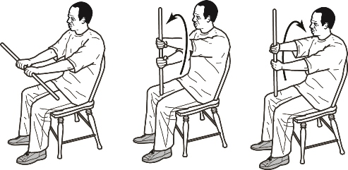 Man sitting in chair holding cane in front, twists cane to left, then right